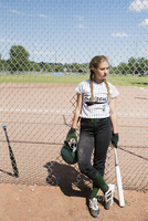 Middle school girl softball player with batting helmet and bat leaning on sunny fence 11096043527| 写真素材・ストックフォト・画像・イラスト素材|アマナイメージズ