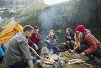 Friends laughing and hanging out around campfire at remote lakeside 11096044734| 写真素材・ストックフォト・画像・イラスト素材|アマナイメージズ