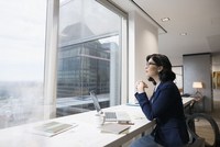 Pensive businesswoman at laptop looking out urban office window 11096045334| 写真素材・ストックフォト・画像・イラスト素材|アマナイメージズ