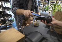 Close up father and daughter paying with smart phone contactless payment at plant shop counter 11096047583| 写真素材・ストックフォト・画像・イラスト素材|アマナイメージズ