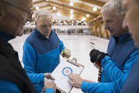 Senior men with clipboard discussing strategy at curling club 11096048332| 写真素材・ストックフォト・画像・イラスト素材|アマナイメージズ