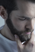 Close up portrait pensive brunette Caucasian young man with beard thinking, looking down with hand on chin 11096048869| 写真素材・ストックフォト・画像・イラスト素材|アマナイメージズ