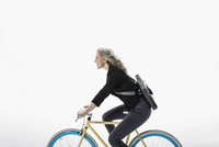 Smiling businesswoman riding bicycle against white background 11096049067| 写真素材・ストックフォト・画像・イラスト素材|アマナイメージズ