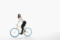 Playful businesswoman riding bicycle against white background 11096049068| 写真素材・ストックフォト・画像・イラスト素材|アマナイメージズ