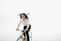 Smiling businesswoman riding bicycle against white background 11096049069| 写真素材・ストックフォト・画像・イラスト素材|アマナイメージズ