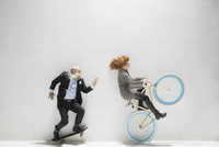 Businessman on skateboard and businesswoman riding bicycle against white background 11096049076| 写真素材・ストックフォト・画像・イラスト素材|アマナイメージズ