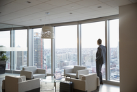 Pensive businessman with suitcase at window in highrise lounge, looking at view 11096049604| 写真素材・ストックフォト・画像・イラスト素材|アマナイメージズ