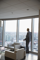 Pensive businessman with suitcase at window in highrise lounge, looking at view 11096049605| 写真素材・ストックフォト・画像・イラスト素材|アマナイメージズ
