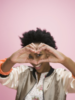 Portrait African American young woman forming heart-shape with hands against pink background 11096050321| 写真素材・ストックフォト・画像・イラスト素材|アマナイメージズ