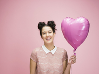 Portrait smiling young brunette woman holding pink heart-shape balloon against pink background 11096050325| 写真素材・ストックフォト・画像・イラスト素材|アマナイメージズ