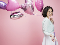 Portrait smiling young brunette woman carrying heart-shape bunch balloons against pink background 11096050350| 写真素材・ストックフォト・画像・イラスト素材|アマナイメージズ