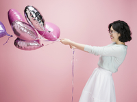 Young brunette woman pulling at balloons against pink background 11096050351| 写真素材・ストックフォト・画像・イラスト素材|アマナイメージズ