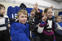 Portrait confident boy and girl ice hockey players cheering and celebrating in locker room 11096050588| 写真素材・ストックフォト・画像・イラスト素材|アマナイメージズ