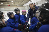Coach and boy and girl ice hockey players joining hands in huddle 11096050625| 写真素材・ストックフォト・画像・イラスト素材|アマナイメージズ
