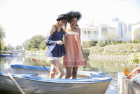 Smiling young women standing in summer rowboat on lake 11096054000| 写真素材・ストックフォト・画像・イラスト素材|アマナイメージズ