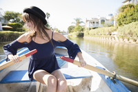 Smiling young woman in dress rowing boat on sunny summer lake 11096054006| 写真素材・ストックフォト・画像・イラスト素材|アマナイメージズ