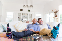 Comfortable male gay couple in striped socks relaxing, watching TV on living room sofa 11096054068| 写真素材・ストックフォト・画像・イラスト素材|アマナイメージズ