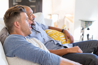 Male gay couple relaxing, watching TV on living room sofa 11096054076| 写真素材・ストックフォト・画像・イラスト素材|アマナイメージズ