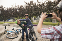 Boy photographing friends on bicycles in park 11096054401| 写真素材・ストックフォト・画像・イラスト素材|アマナイメージズ