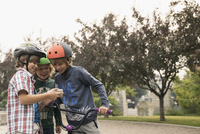 Boy friends on bicycle using cell phone in park 11096054402| 写真素材・ストックフォト・画像・イラスト素材|アマナイメージズ