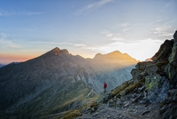 Hiker looking over a beatiful valley in the sunset 11098082021| 写真素材・ストックフォト・画像・イラスト素材|アマナイメージズ