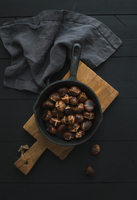 Roasted chestnuts in iron skillet pan on rustic wooden board over black table background, top view. 11098082634| 写真素材・ストックフォト・画像・イラスト素材|アマナイメージズ