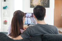 Young Asian couple waching movie on tv at home 11098082927| 写真素材・ストックフォト・画像・イラスト素材|アマナイメージズ