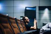 Young adult man waiting in airport lounge using smart phone 11098086421| 写真素材・ストックフォト・画像・イラスト素材|アマナイメージズ