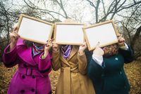 Women holding blank frames in front of faces 11100003320| 写真素材・ストックフォト・画像・イラスト素材|アマナイメージズ
