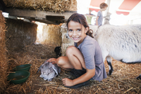 Girl (6-7) with rabbit and goat on straw,  looking at camera 11100004529| 写真素材・ストックフォト・画像・イラスト素材|アマナイメージズ