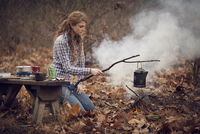 Young woman cooking in forest 11100008367| 写真素材・ストックフォト・画像・イラスト素材|アマナイメージズ