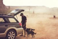 USA, Arizona, Monument Valley, Young man with dogs looking in car trunk in desert 11100029798| 写真素材・ストックフォト・画像・イラスト素材|アマナイメージズ