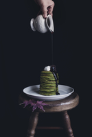 Brown sugar syrup being poured on matcha pancakes in plate on table against black background 11100037751| 写真素材・ストックフォト・画像・イラスト素材|アマナイメージズ