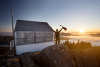 Rear view of man holding guitar while standing by log cabin on mountain during sunset 11100042767| 写真素材・ストックフォト・画像・イラスト素材|アマナイメージズ