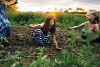 Girl with sisters shouting while crouching in mud 11100042898| 写真素材・ストックフォト・画像・イラスト素材|アマナイメージズ
