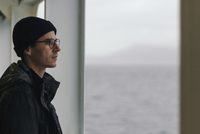 Thoughtful man looking away while standing in cruise ship 11100048737| 写真素材・ストックフォト・画像・イラスト素材|アマナイメージズ