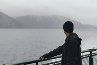 Man looking at view while standing by railing in cruise ship 11100048741| 写真素材・ストックフォト・画像・イラスト素材|アマナイメージズ