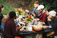 High angle view of friends eating food while sitting at dining table in backyard 11100050611| 写真素材・ストックフォト・画像・イラスト素材|アマナイメージズ