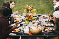 Friends eating food while sitting at dining table in backyard 11100050612| 写真素材・ストックフォト・画像・イラスト素材|アマナイメージズ