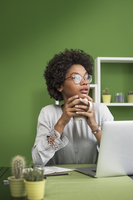 Thoughtful woman with laptop computer having coffee at office 11100050751| 写真素材・ストックフォト・画像・イラスト素材|アマナイメージズ