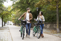 Couple talking while walking with bicycle on road at park 11100050984| 写真素材・ストックフォト・画像・イラスト素材|アマナイメージズ