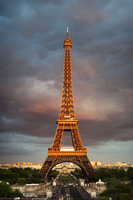 Low angle view of Eiffel Tower against cloudy sky during sunset 11100051696| 写真素材・ストックフォト・画像・イラスト素材|アマナイメージズ