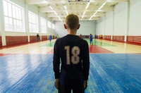 Rear view of player standing at indoor soccer court 11100051856| 写真素材・ストックフォト・画像・イラスト素材|アマナイメージズ