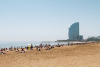 Tourist relaxing at beach by W Barcelona hotel against clear sky 11100052235| 写真素材・ストックフォト・画像・イラスト素材|アマナイメージズ