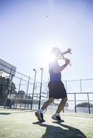 Low angle view of man playing tennis in court on sunny day 11100052793| 写真素材・ストックフォト・画像・イラスト素材|アマナイメージズ