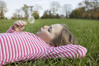 Side view of girl blowing dandelion while lying on grassy field in park 11100053046| 写真素材・ストックフォト・画像・イラスト素材|アマナイメージズ