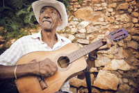 Man playing guitar while sitting against stone wall 11100054060| 写真素材・ストックフォト・画像・イラスト素材|アマナイメージズ