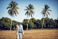 Man carrying hand tool while walking on field against blue sky 11100054090| 写真素材・ストックフォト・画像・イラスト素材|アマナイメージズ