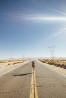 Rear view of woman walking on road by desert during sunny day 11100057113| 写真素材・ストックフォト・画像・イラスト素材|アマナイメージズ