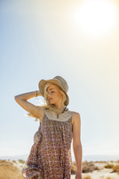 Woman in sun hat standing against clear sky during sunny day 11100057116| 写真素材・ストックフォト・画像・イラスト素材|アマナイメージズ